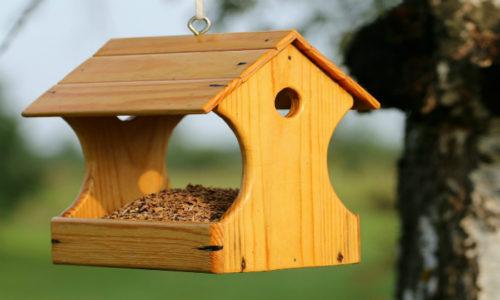 Классическая кормушка — это домик из дерева, который представляет собой площадку с невысокими краями, накрытую двумя листами фанеры или тонкой вагонки на манер двускатной крыши